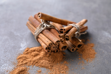 Aromatic cinnamon sticks and powder on grey background