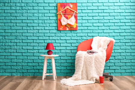 Stylish armchair near color wall in interior