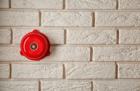 Modern alarm bell on brick wall indoors