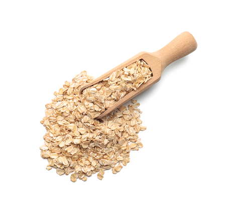 Scoop with raw oatmeal on white background