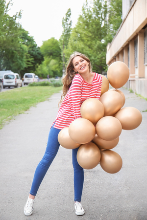 Beautiful young woman with balloons outdoors