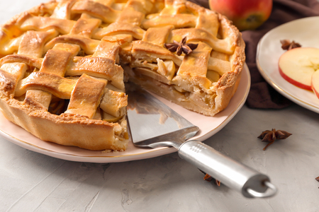 Plate with delicious apple pie on grey background, closeup