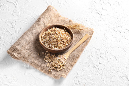 Bowl and spoon with raw oatmeal on light background
