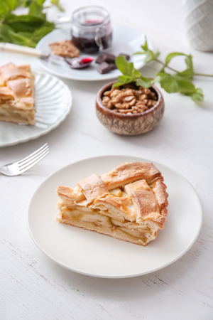 Plate with piece of delicious apple pie on wooden table