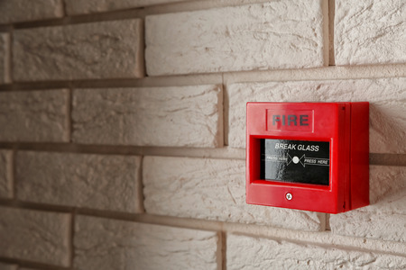 Modern fire call point on brick wall indoors