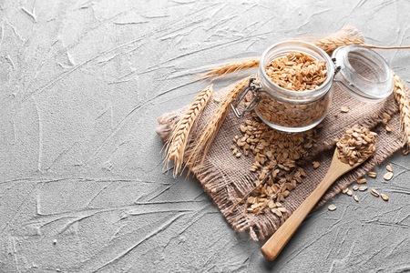 Glass jar with raw oatmeal and spoon on light textured background