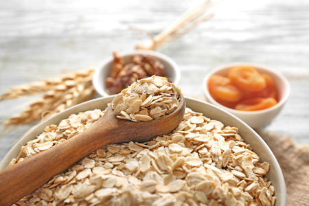 Bowl with oatmeal flakes on table, closeup