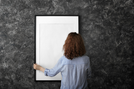 Woman hanging blank photo frame on dark wall Standard-Bild