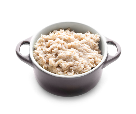 Tasty oatmeal in bowl on white background