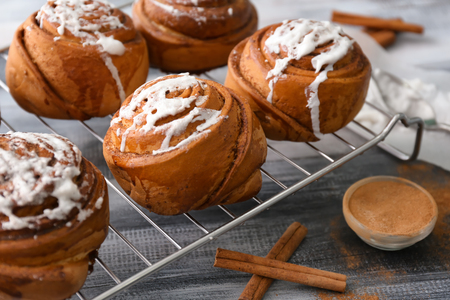 Cooling rack with delicious cinnamon buns on wooden background, closeup Archivio Fotografico
