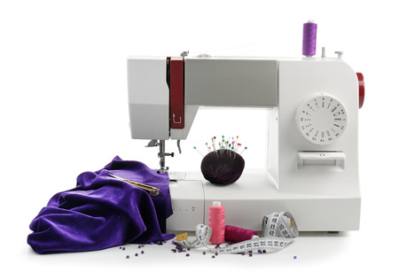 Máquina de coser moderna con accesorios de sastre sobre fondo blanco.