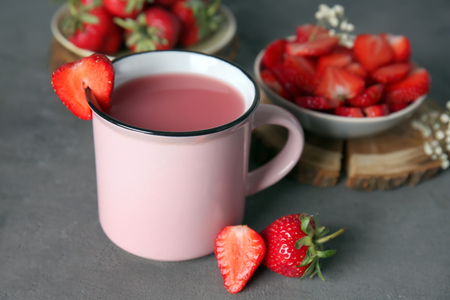 Cup with tasty strawberry starch drink on grey table 免版税图像