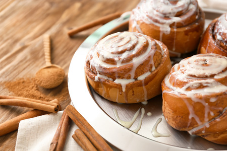 Plate with tasty cinnamon buns on wooden table, closeup