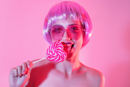 Young woman with unusual hair and lollipop on color background 스톡 콘텐츠