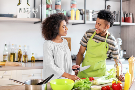 Young African-American couple cooking together in kitchen