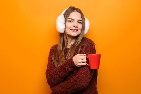 Beautiful young woman in warm sweater holding cup of hot tea on color background