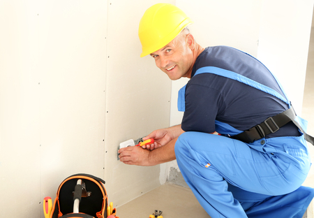 Male electrician repairing socket in flat Stock Photo