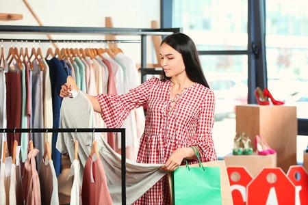Beautiful young woman choosing clothes in shop