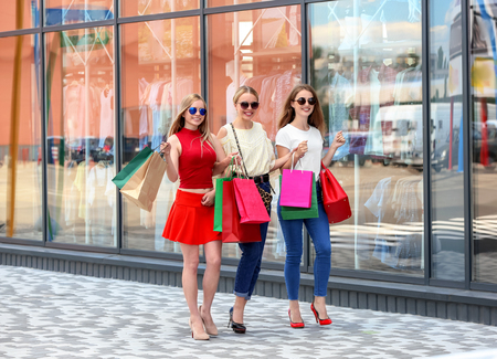 Young women with shopping bags walking on city street