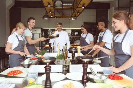 Chef et groupe de jeunes pendant les cours de cuisine Banque d'images