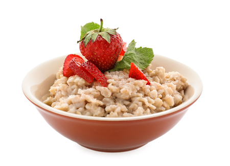 Bowl with prepared oatmeal and strawberry on white background