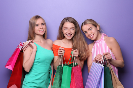 Beautiful young women with shopping bags on color background