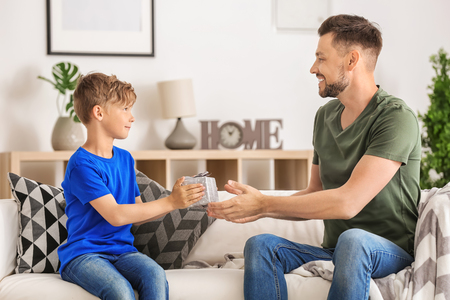 Man receiving gift for Fathers Day from his son at home Stock Photo