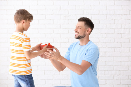 Man receiving gift for Father's Day from his son on light background