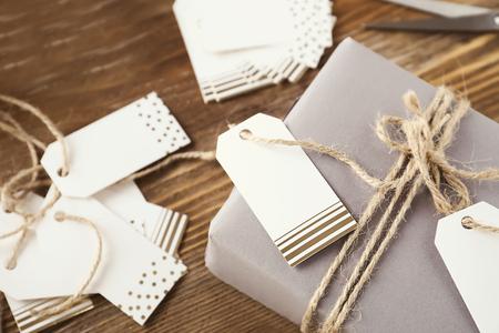 Wrapped gift and paper labels for scrapbooking on wooden background