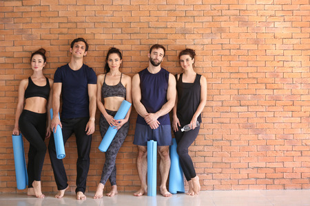 Group of people with yoga mats near brick wall
