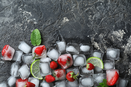 Ice cubes with strawberries and lime slices on grey background Reklamní fotografie
