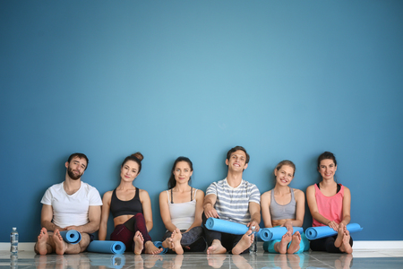 Group of people with yoga mats sitting on floor near color wall 版權商用圖片