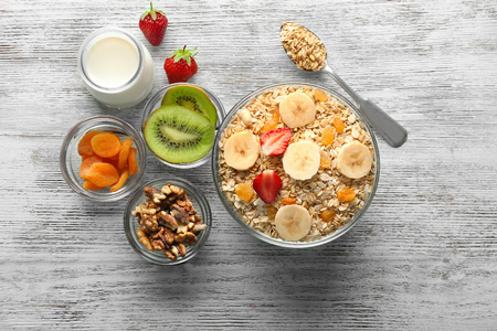 Bowl with raw oatmeal, milk, fruits and nuts on wooden table