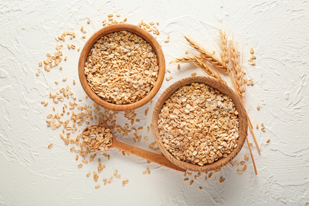 Bowls with raw oatmeal on light background