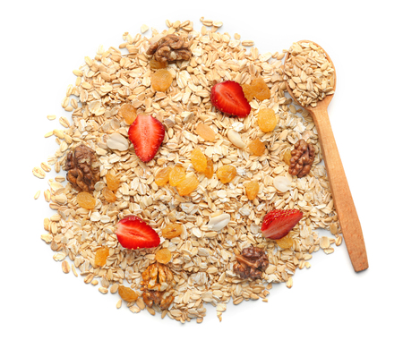Heap of raw oatmeal with raisins, walnut and strawberry on white background