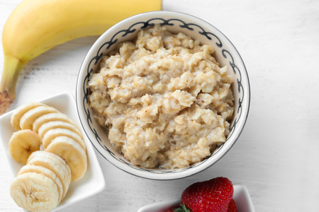 Bowl with tasty oatmeal, banana and strawberries on table Stok Fotoğraf