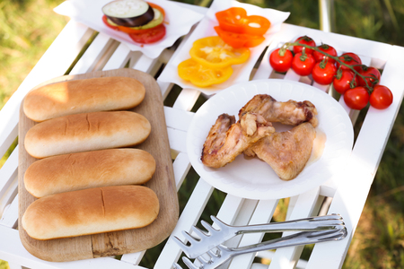 Plates with grilled chicken wings, vegetables and bread on table outdoors prepared for summer picnic