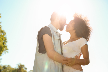 Young loving interracial couple outdoors on spring day Stock Photo