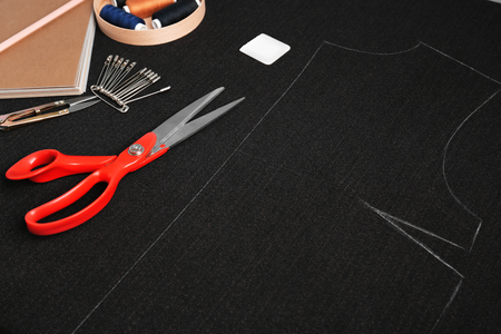 Scissors with notebook and sewing accessories on dark fabric