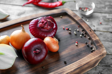 Board with fresh onion and spices on wooden background