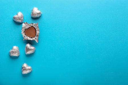 Heart-shaped chocolate candies on color background