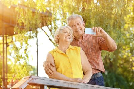 Happy mature couple taking selfie in park 版權商用圖片