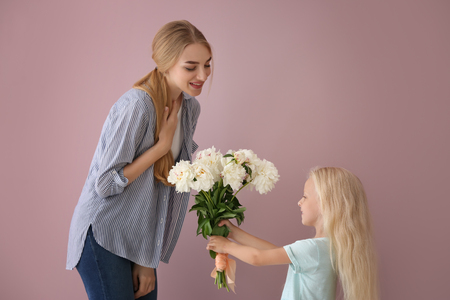 Cute little girl giving flowers to her mother on color background Stock Photo