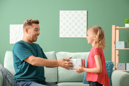 Cute little girl greeting her daddy with Fathers Day at home