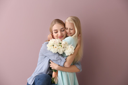 Attractive young woman and cute little girl with beautiful flowers on color background