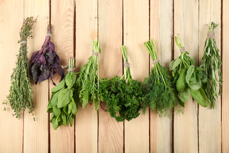 Bunches of different herbs on wooden background