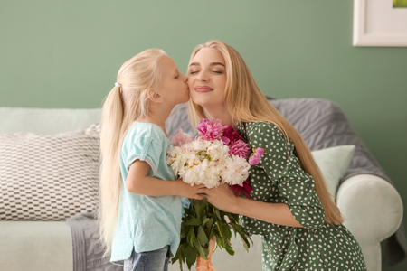 Attractive young woman and her cute little daughter with beautiful flowers at home