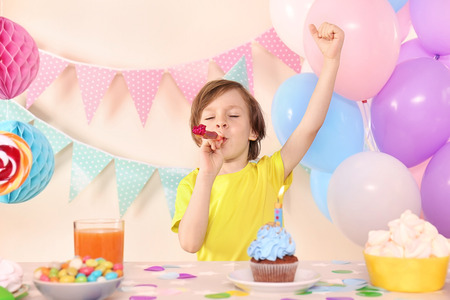 Cute little boy with party whistle celebrating Birthday at home