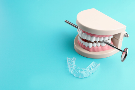 Artificial jaw, dental mirror and occlusal splint on color background Stok Fotoğraf