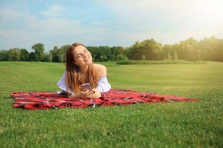 Young woman listening to music on plaid outdoors